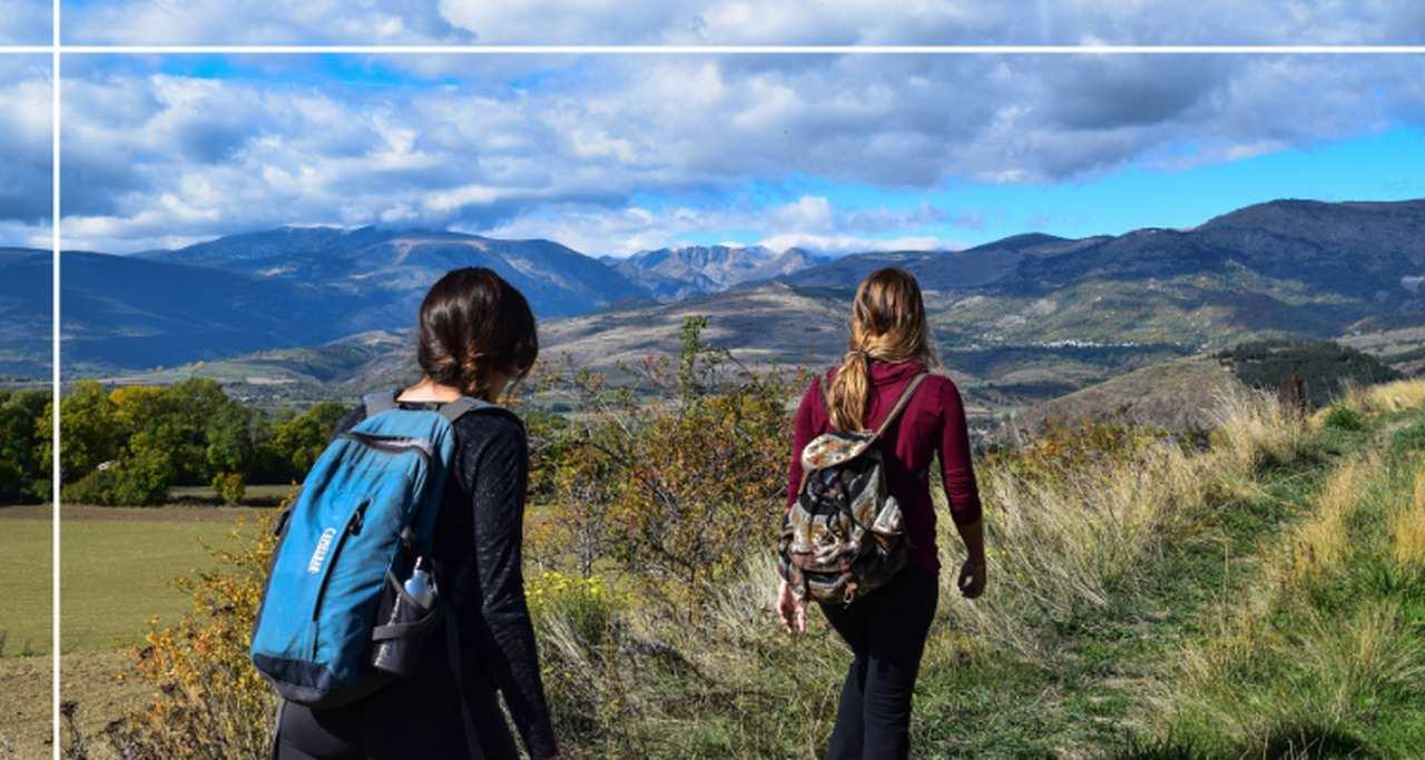 dwie kobiety wędrujące z plecakami po górach